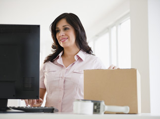 Smiling Hispanic woman with cardboard box using computer