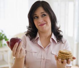 Smiling Hispanic woman choosing between cookies and apple