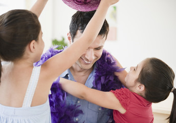 Daughters dressing father in feather boa and hat