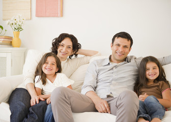 Happy family sitting on sofa together