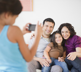Daughter taking smiling family's photograph