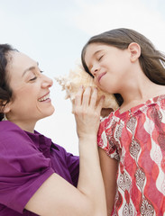 Mother holding seashell to daughter's ear