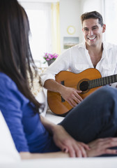 Mixed race man playing guitar for wife