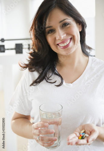 Smiling Hispanic woman taking vitamins