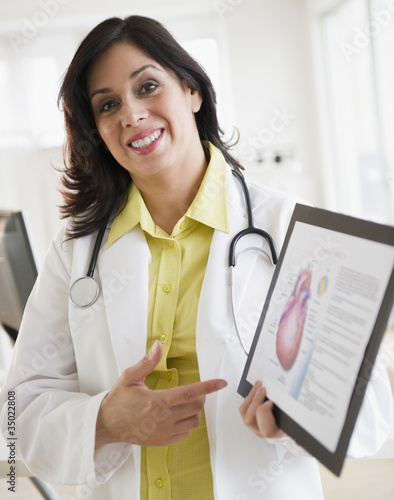 Smiling Hispanic doctor holding up diagram of heart