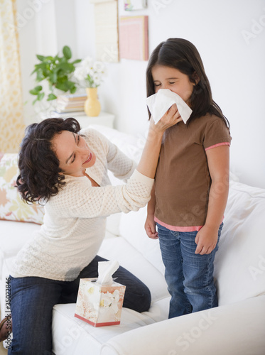 Mother wiping sick daughter's nose with tissue