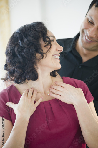 Smiling man giving wife elegant necklace