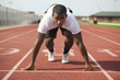 Black athlete kneeling at track starting line