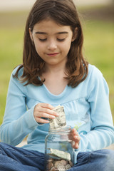 Caucasian girl taking money from jar