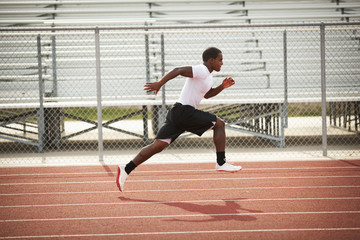 Black athlete running on track