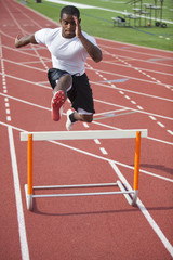 Black athlete jumping over hurdle on track
