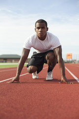 Black athlete crouching at track starting line