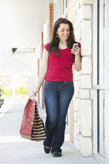 Hispanic woman carrying shopping bags and using cell phone