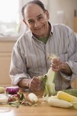 Senior Hispanic man shucking corn