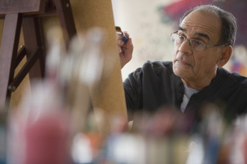 Senior Hispanic man painting on easel