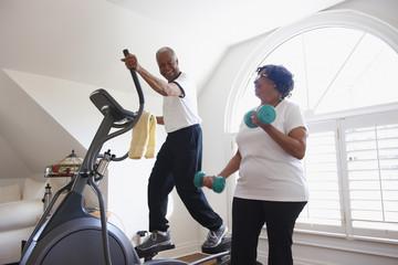 """Smiling Black man using elliptical machine, wife using hand weights"""