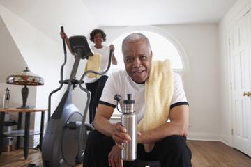 """Black woman using elliptical machine, husband drinking water"""