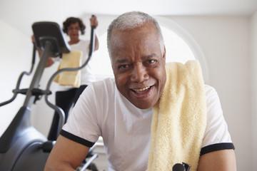"""Black woman using elliptical machine, husband resting"""