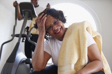 """Black man using elliptical machine, wife resting"""