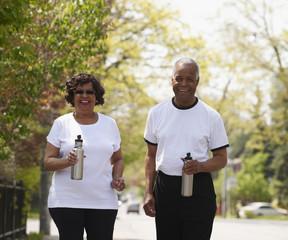 Black couple walking together holding water bottles