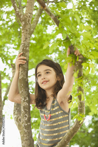 Caucasian girl climbing in tree