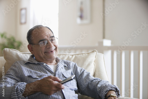 Senior Hispanic man using remote control