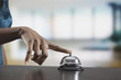 Black woman ringing reception desk bell