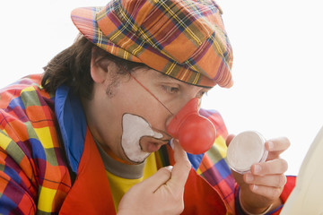 Hispanic man putting on clown makeup