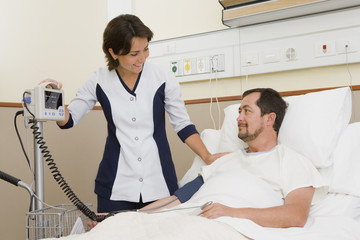 Nurse taking patient's blood pressure in hospital room