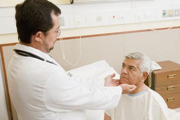 Doctor examining patient's throat in hospital room