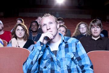 Caucasian man watching movie in theater