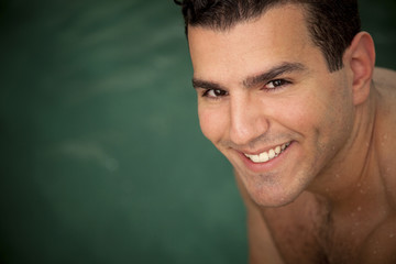 Smiling Middle Eastern man near swimming pool
