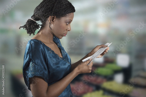 Black woman looking at grocery shopping list