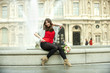 Caucasian woman sitting on fountain with bouquet at the Louvre