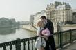 Caucasian couple kissing on bridge