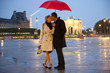 Caucasian couple kissing in rain at night near the Louvre