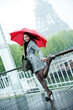 Caucasian woman in high heel shoes with red umbrella near Eiffel Tower