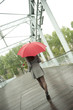 Caucasian woman walking in rain with red umbrella