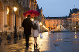 Caucasian couple walking in rain at night at the Louvre