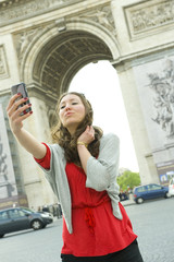 Caucasian woman taking self-portrait near Arc de Triomphe