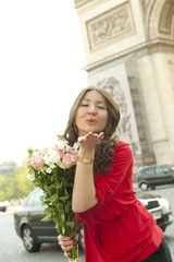 Caucasian woman holding bouquet and blowing kisses near Arc de Triomphe