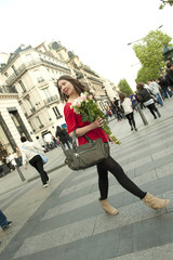 Caucasian woman walking and holding bouquet