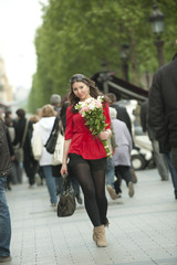 Smiling Caucasian woman walking with bouquet