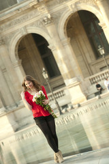 Caucasian woman standing near fountain with bouquet at the Louvre