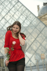 Caucasian woman standing  at the Louvre with rose