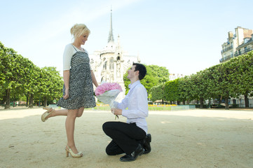 Caucasian man proposing to girlfriend in park near Notre Dame