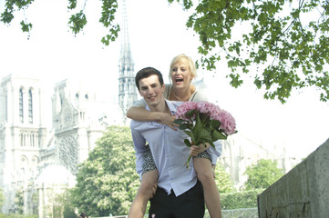 Caucasian man giving girlfriend piggyback ride near Notre Dame
