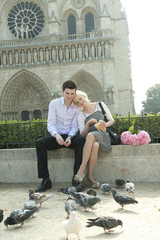 Caucasian couple feeding pigeons near Notre Dame