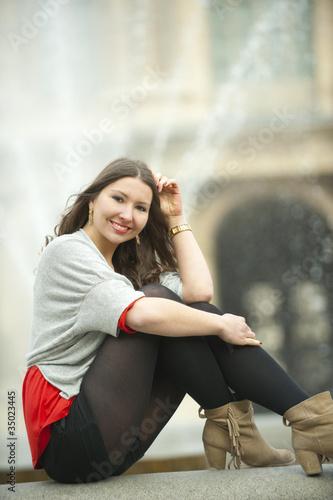 Caucasian woman sitting near fountain