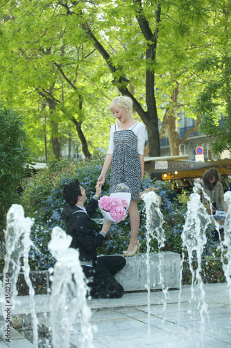 Caucasian man proposing to girlfriend near fountain